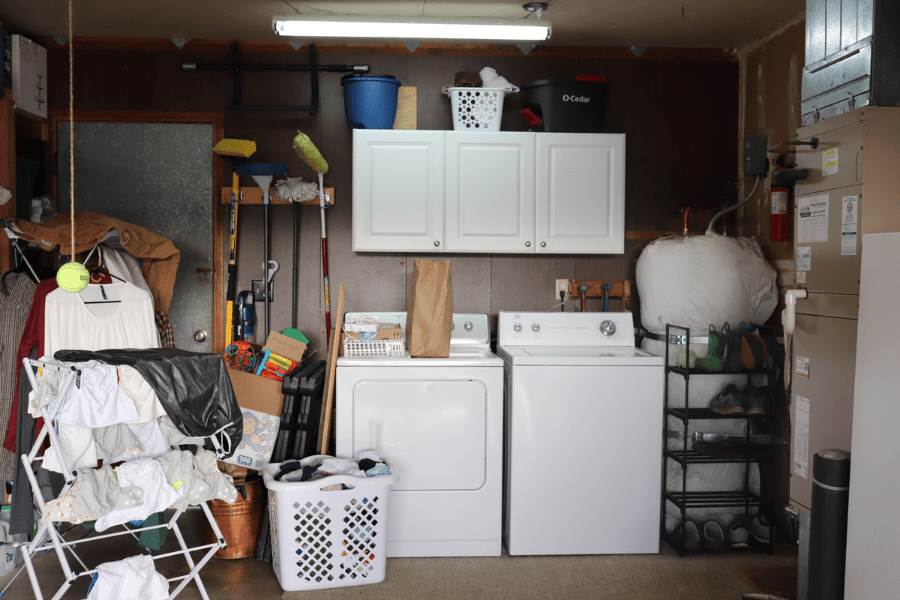 a garage laundry area with hanging laundry on a drying rack, a white laundry basket, a white washer and dryer, white cabinets, a black shoe rack, a water heater to the right and a metal door to the left. A blue bucket, white basket and black mop bucket on top of the cupboards.