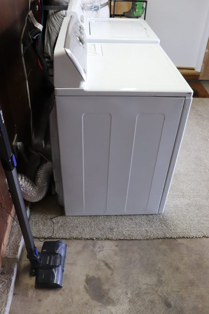 A laundry area with a grey and purple cordless vacuum and the side of a white washer and dryer