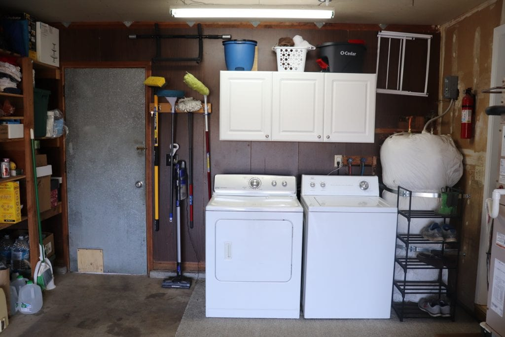 Laundry area, white washer and dryer and white cabinets against a dark paneled wall with a metal door on the left and a water heater on the right, blue bucket, white basket and black mop bucket on top of the cabinets.
