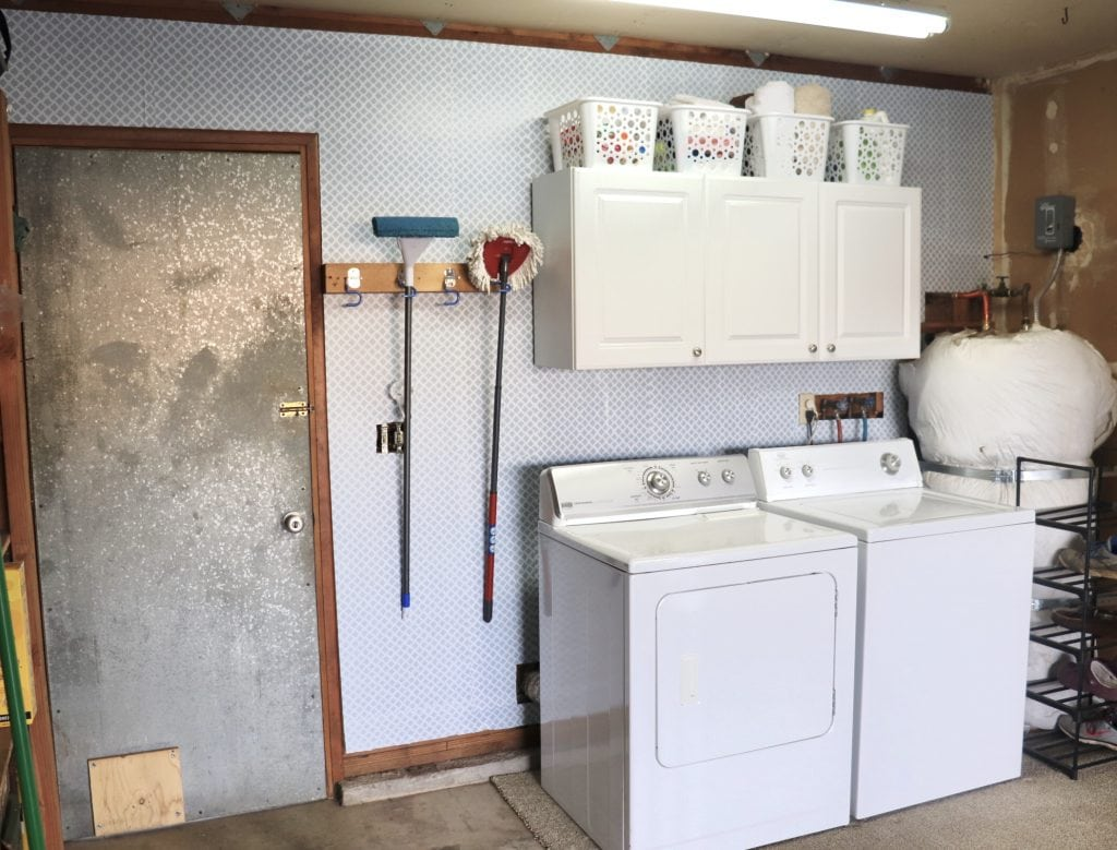 Garage laundry area with white washer and dryer and white cabinets against a grey and white wallpaper wall, metal door on the left, water heater on the right, matching white baskets on top of the cabinets and two mops hanging on the wall