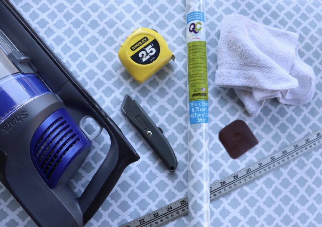 cordless vacuum, tape measure, rag, utility knife, scraper and room of contact paper laid out on a gray and white piece of contact paper