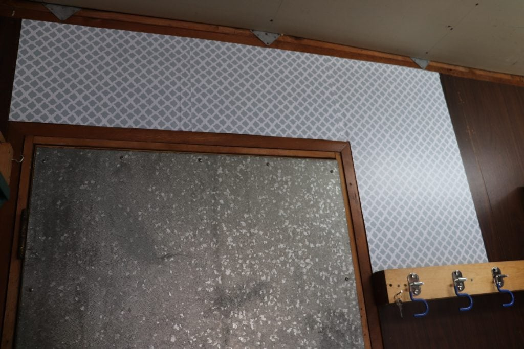 Grey and white patterned contact paper applied to a dark paneled wall over a grey metal door