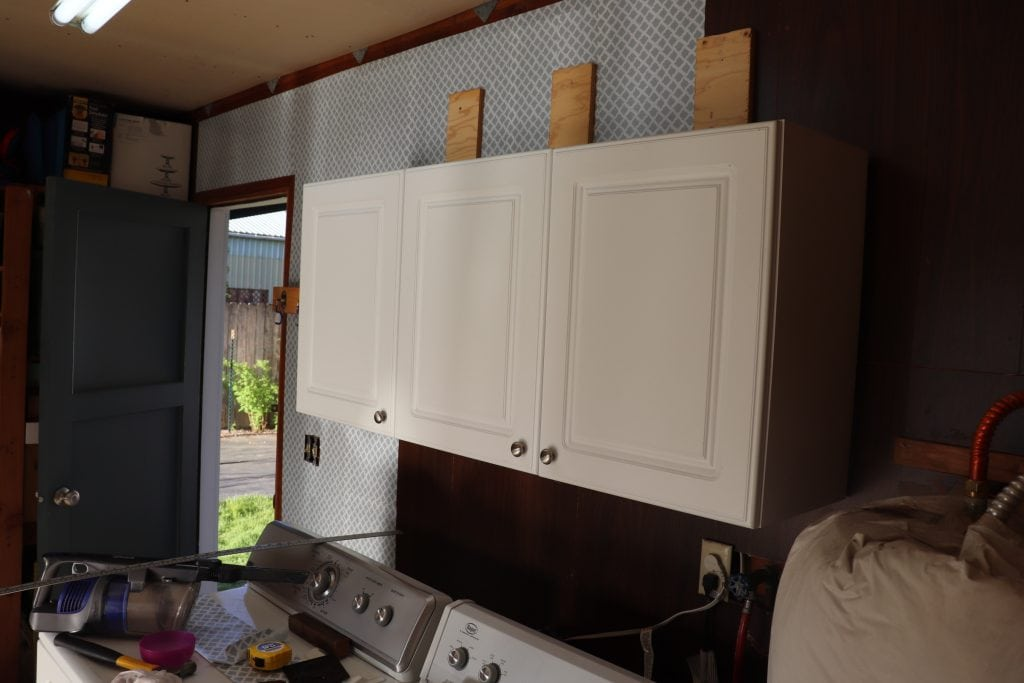 white cabinets against a dark paneled wall with water heater and white washer and dryer in the foreground, open door on the far side of the wall, half the wall covered in grey and white contact paper