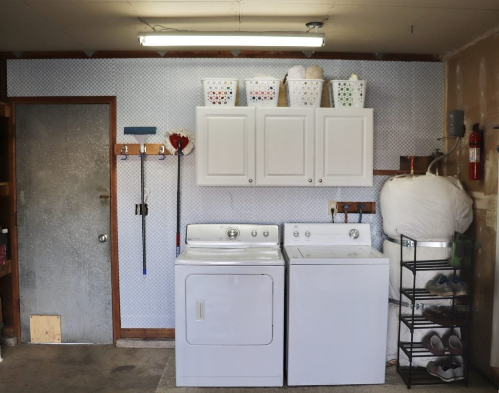 Garage laundry area with white washer and dryer and white cabinets with matching white baskets on top against a wallpapered grey and white patterned wall, metal door on the left, water heater on the right, black shoe rack with some shoes on it in front of water heater.