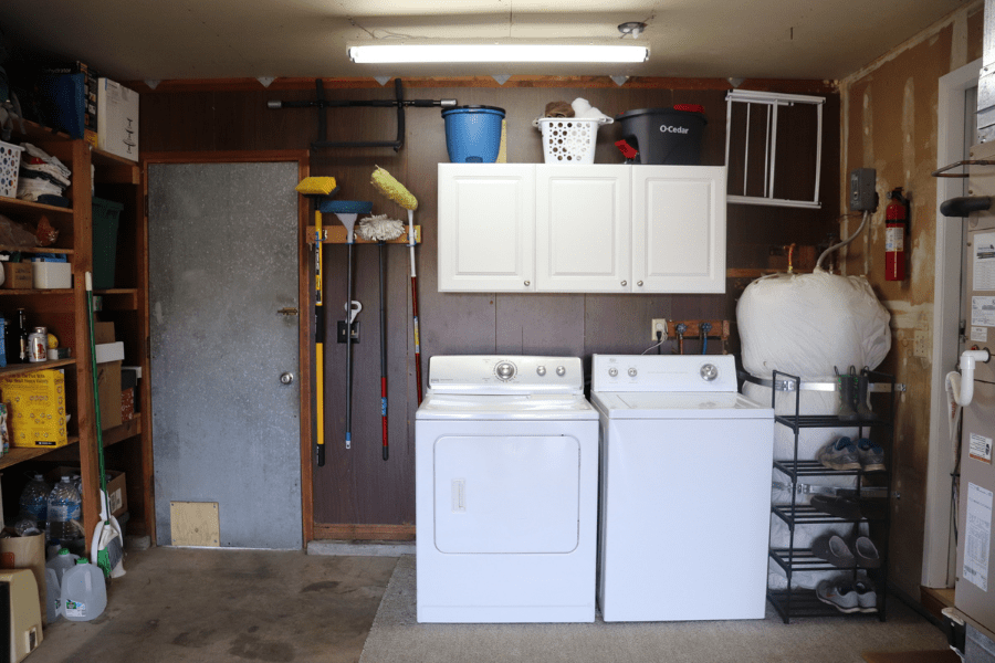 a garage laundry area with a white washer and dryer and white cabinets against a dark paneled wall, a water heater on the right hand side, a metal door on the left, a mop bucket, a blue bucket and a white basket on top of the cabinets