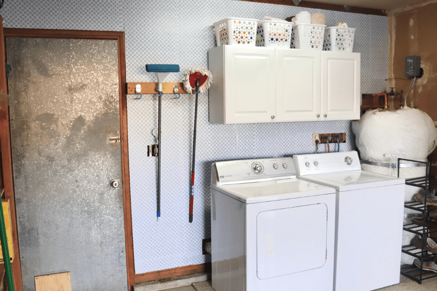 a metal door in a white and gray wallpapered wall, cleaning tools hung on the wall, a white washer and dryer, white cabinets with white baskets lined up on top and a water heater on the right side