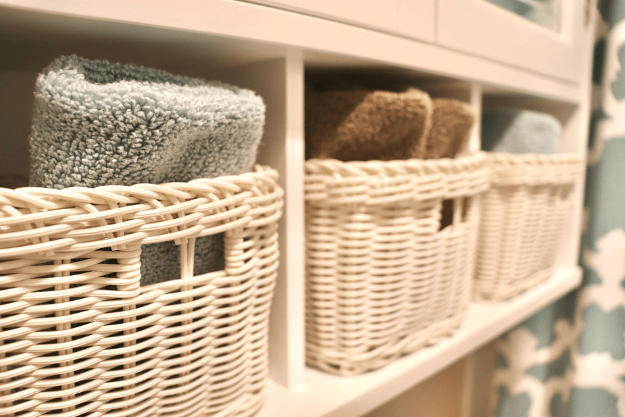 Three white baskets in small white cubby holes with seafoam and brown colored towels rolled up in them