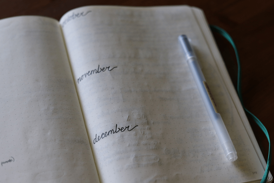 open journal on a wood surface with a pen laying on the page and the months october, november, december handwritten on the page