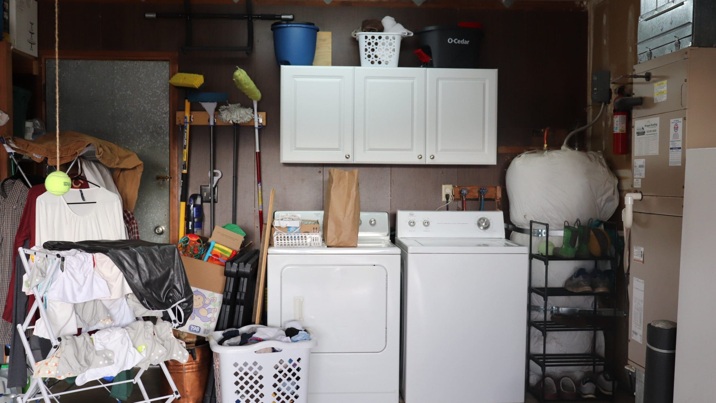 cluttered garage with white wall cabinets, hanging laundry, washer and dryer and water heater against a dark paneled wall
