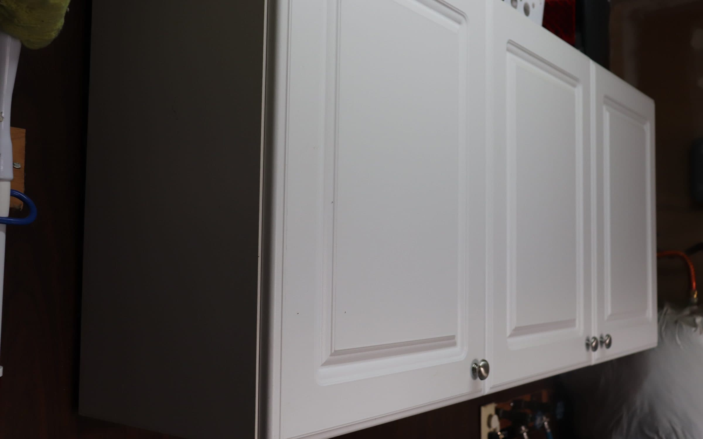 white cabinets with brushed nickel hardware against a dark paneled wall