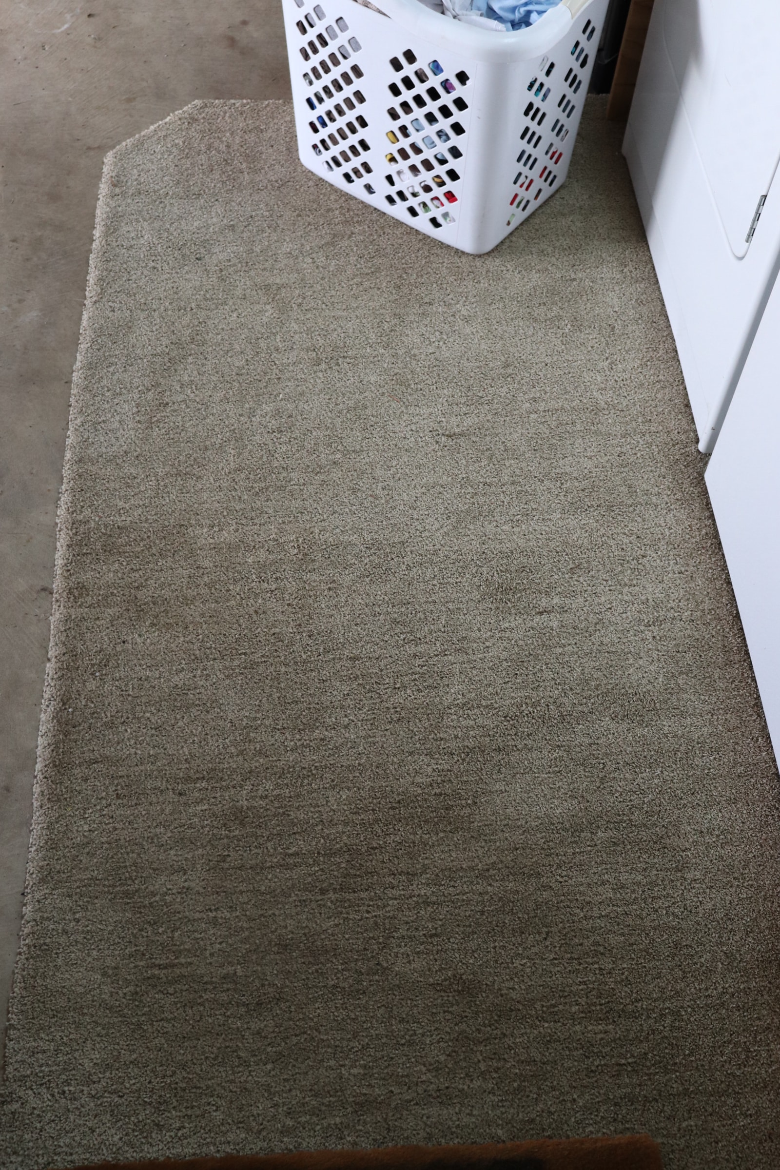 tan carpet with a white laundry basket and a white washer and dryer