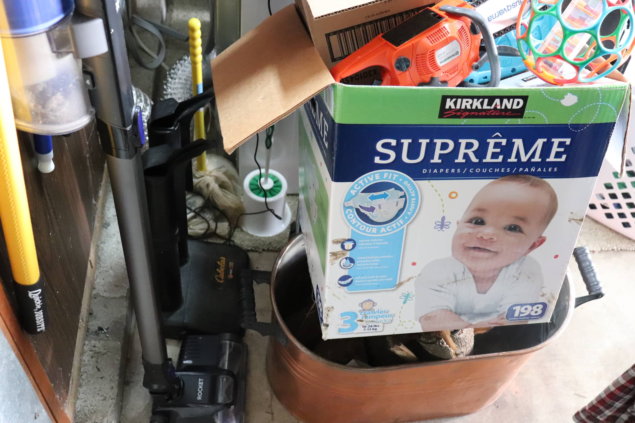 clutter including cordless vacuum,  diaper box filled with toys, copper wash bin