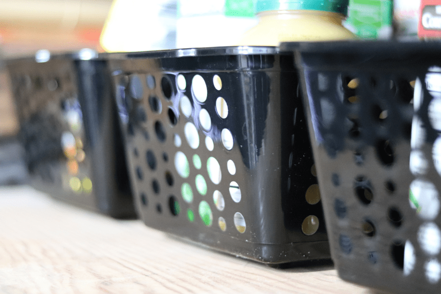 three black plastic baskets lined up on a wood shelf with pantry food in them