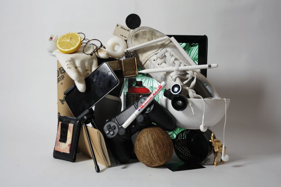 pile of clutter including a smartphone, a shoe, a game controller, a coconut, a tripod, glasses, a lemon slice, a glove, a wallet, earbuds, a book, a tablet and a miniature gold elephant