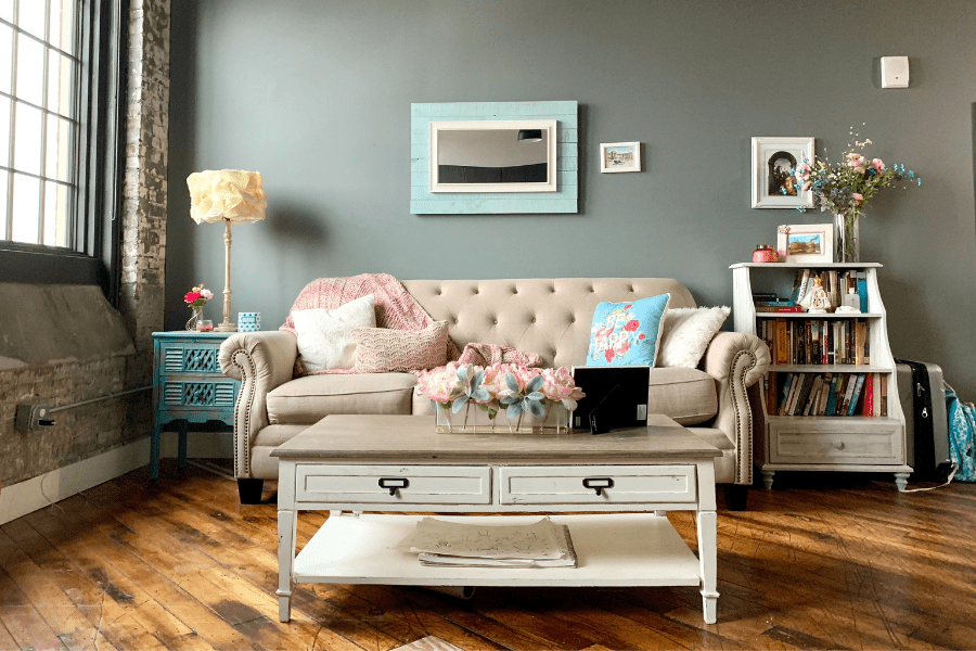 sofa, bookcase, coffee table in living room with a gray wall behind, a floor lamp and a window with brick accents