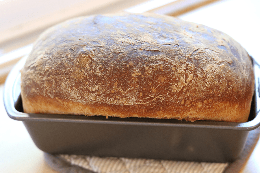 loaf of homemade bread in a loaf pan sitting on a hot pad on a wood surface