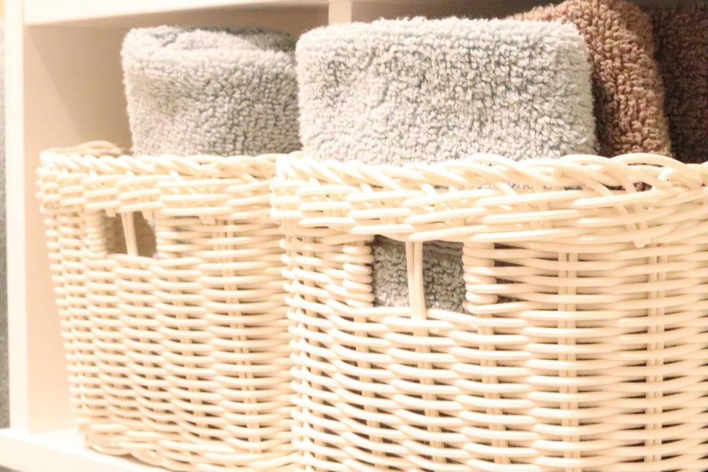 Two white whicker baskets on a white shelf with seafoam green and brown towels rolled up in them
