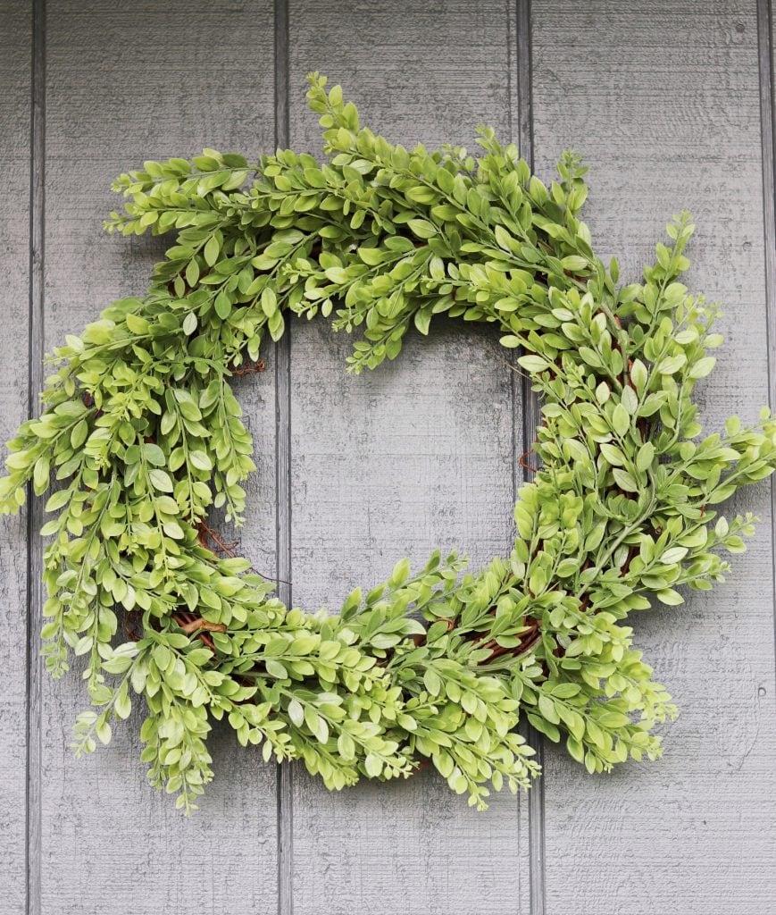 Greenery wreath against dark blue house siding background