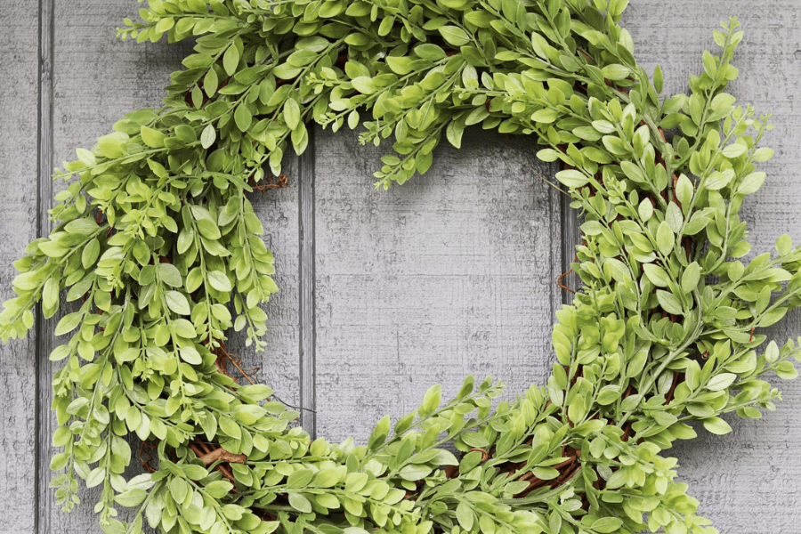 Round greenery wreath hanging against a dark blue house siding background