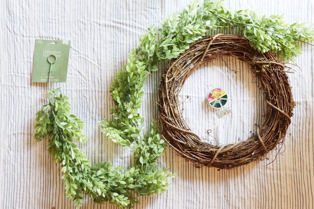 Long greenery garland lying on a blue and white striped background with a grapevine wreath and a spool of floral wire