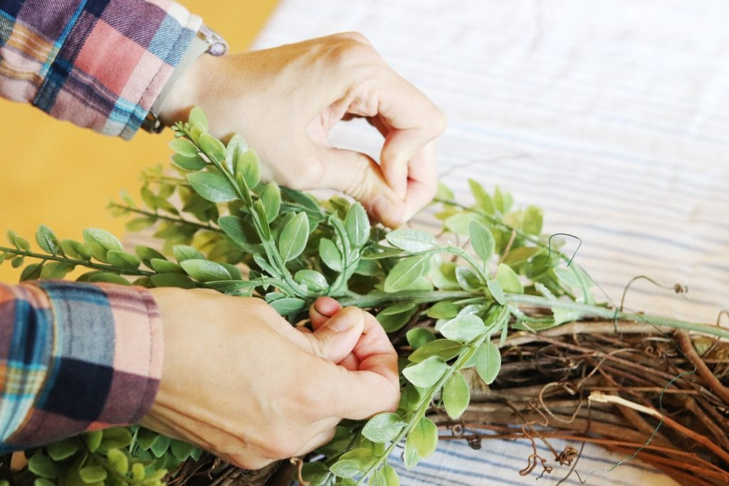 two hands with plaid shirt cuffs above tying floral wire to secure greenery to a grapevine wreath against a blue and white striped background