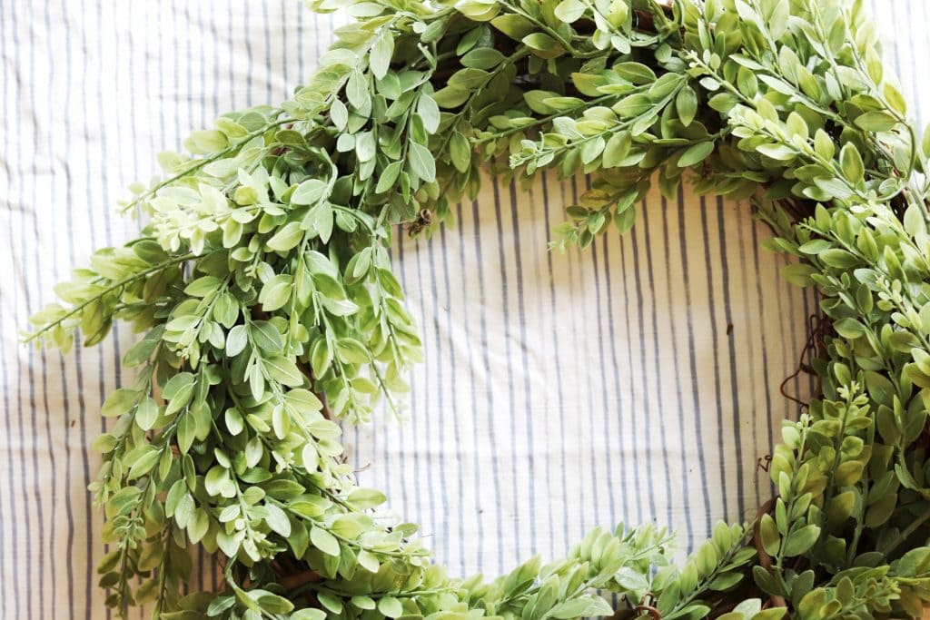Greenery wreath lying against a blue and white striped background