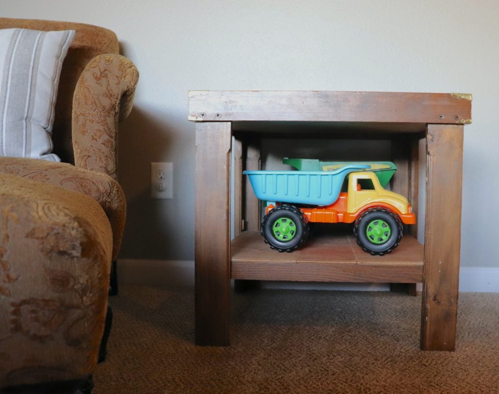 two multi-colored toy dump trucks sitting in the bottom shelf of an end table against a gray wall next to a copper chair with a throw pillow on it and an ottoman