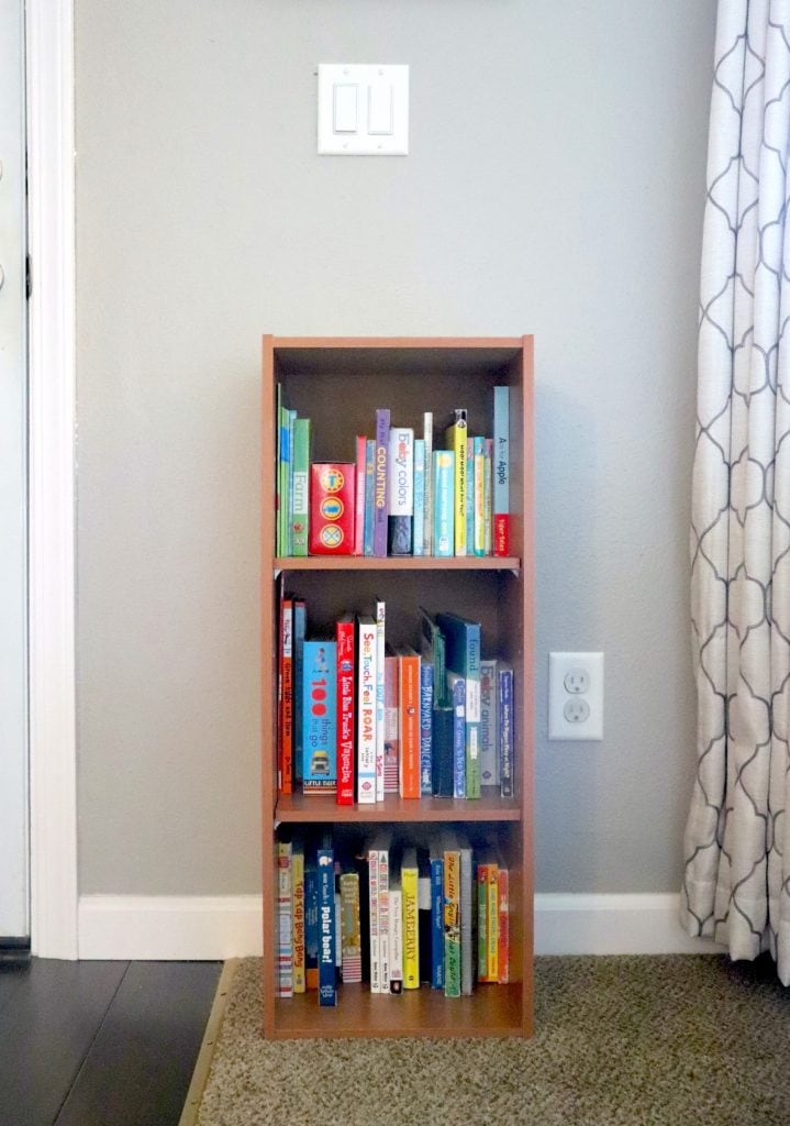 a small bookcase filled with kids board books against a gray wall with a curtain