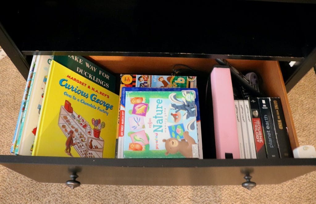 Curious George, Make Way for Ducklings and other children's books along with games and puzzles, DVDs and remotes in an open drawer on a black dresser