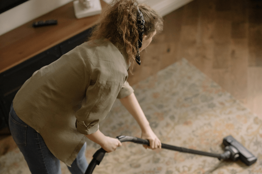 A woman with an olive green shirt and jeans and a curly ponytail vacuuming a rug with a hose vacuum cleaner