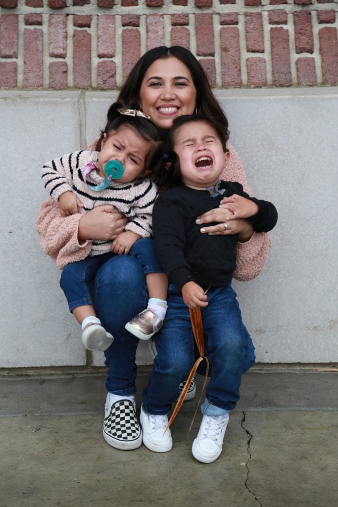 A dark-haired woman holding a baby and a crying toddler against the background of a brick wall