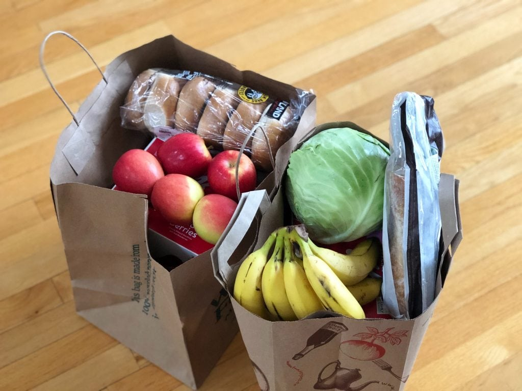 Two paper grocery bags on a wood floor background filled with lettuce, bananas, apples, bagels and a pizza crust