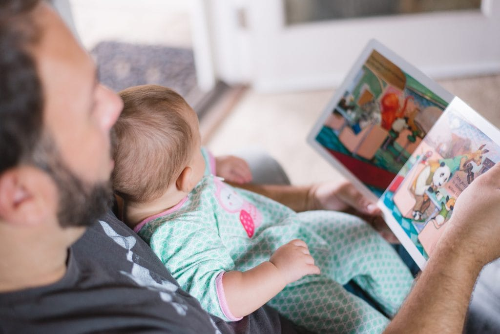 bearded man holding a baby in a green sleeper. They are looking at a children's book together.