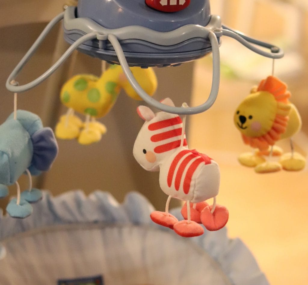A close-up of a baby mobile on a blue baby swing with an elephant, a giraffe, a zebra and a lion hanging down from it