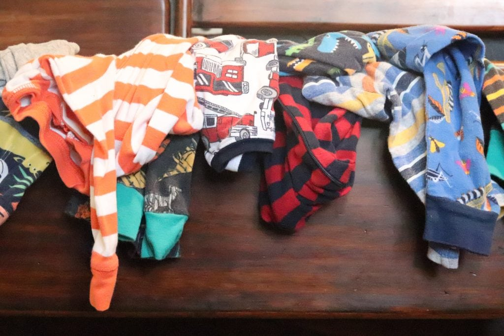 an orange and white striped baby sleeper, a blue and red striped  baby sleeper and several other printed baby pajamas overflowing from the top of a dark wooden drawer