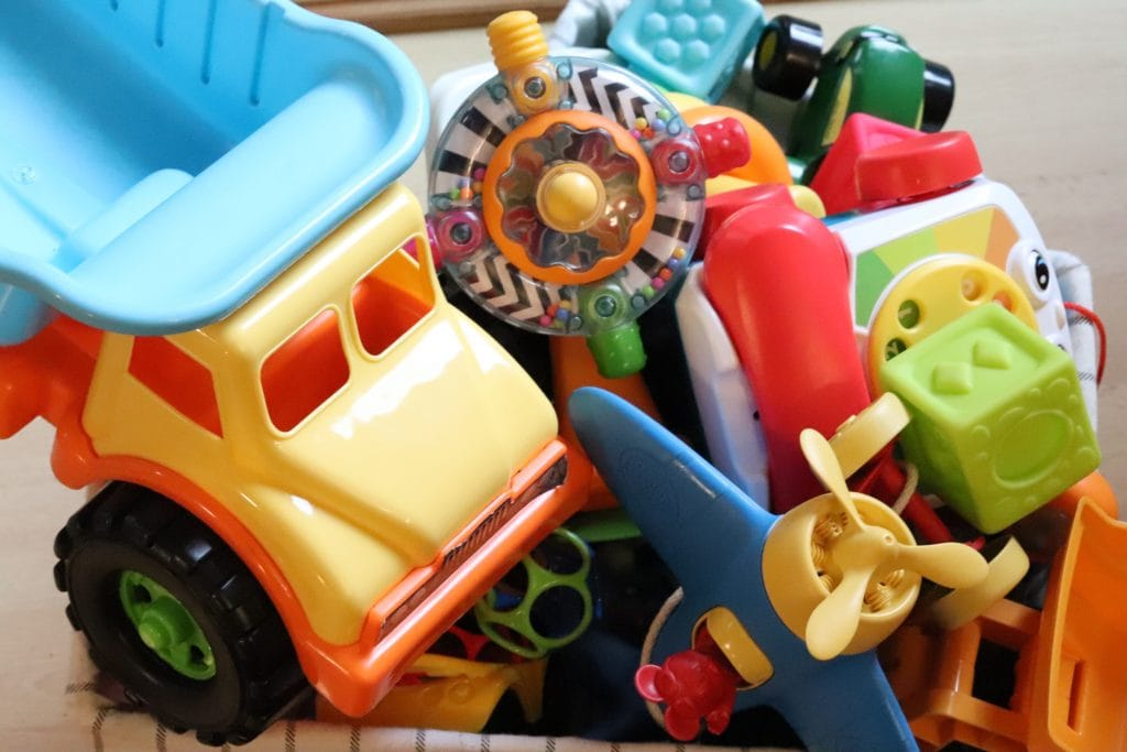 A yellow and blue toy dump truck, a blue and yellow toy airplane, a multi-colored spinning toy, a green block and more toy clutter all stacked together on top of a wood surface background