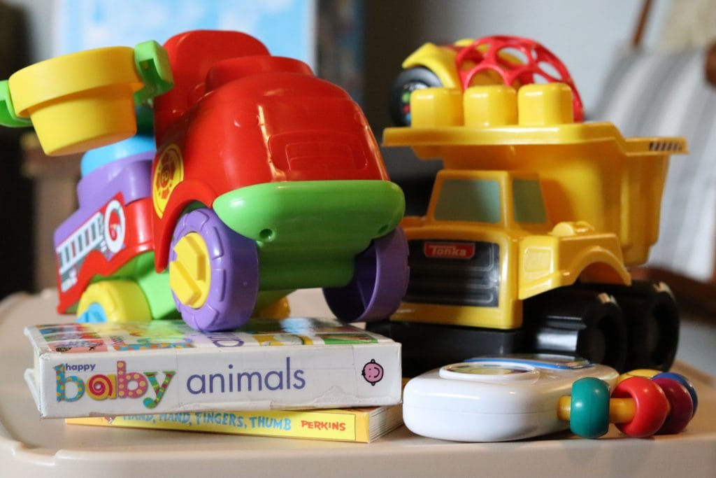 a red plastic toy fire engine with a cherry picker attachment, a baby animals book, a music-playing mini white toy, a toy yellow dump truck and a toy hello and red racer all arranged together on a wood surface
