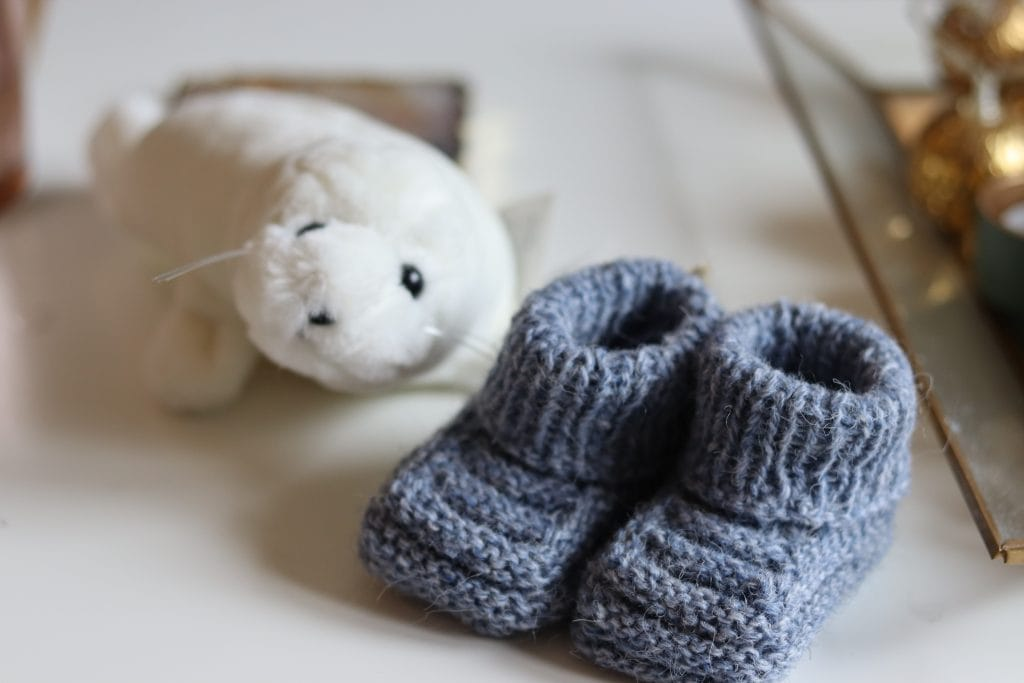 a white seal stuffed animal and  a pair of gray baby booties on a white background