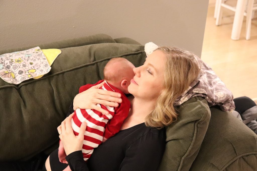 a blonde woman in black and a newborn baby in red and white strips resting on a green couch, the woman is holding the baby