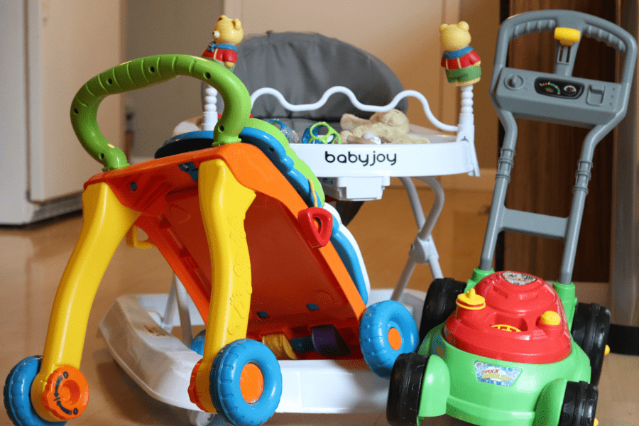 Yellow, orange and green sit and stand toy, white and grey baby walker and red and green and gray toy lawnmower all grouped together on a kitchen wood floor with a white refrigerator and white door in the background
