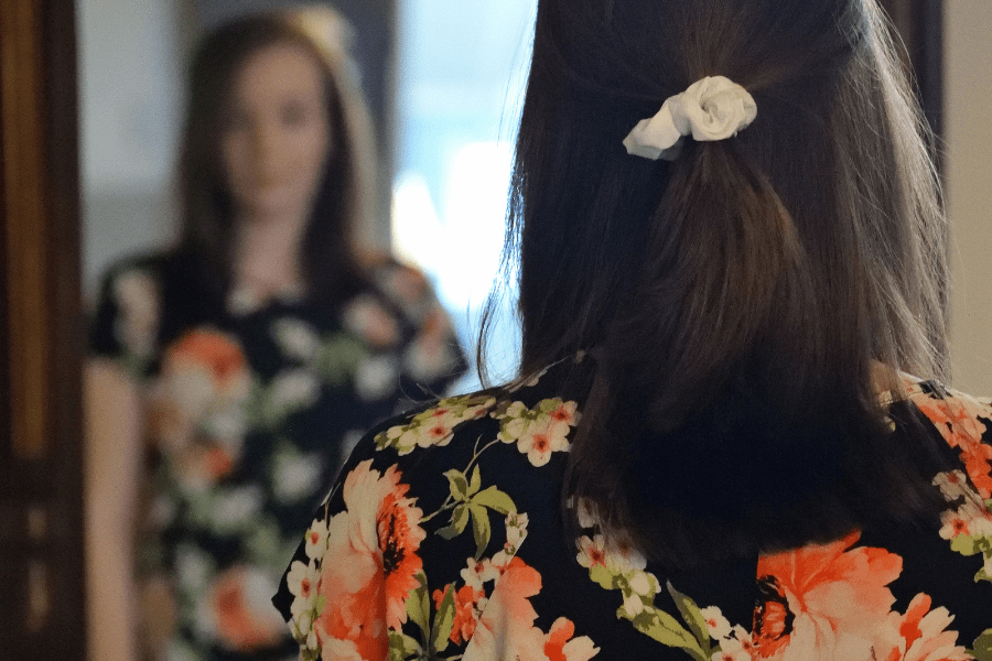 Brunette woman standing in front of a mirror wearing a floral short-sleeve shirt