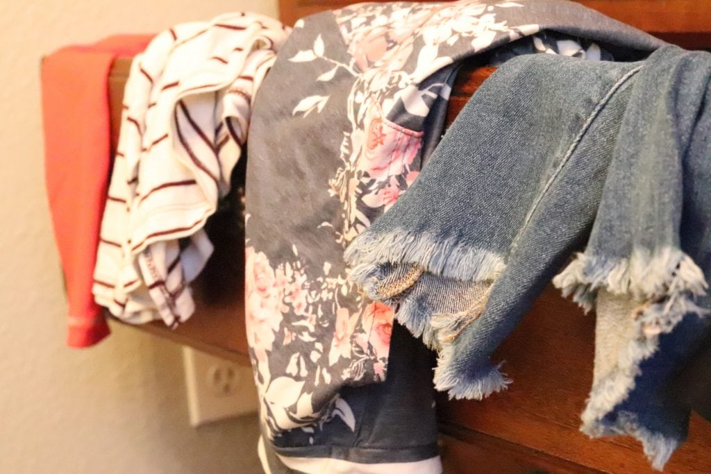 Clothes hanging over the edge of a brown dresser drawer