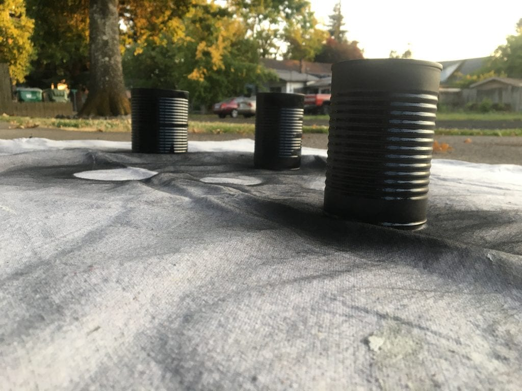 3 black spray painted tin cans sitting on a canvas drop cloth with trees, cars and a house in the background
