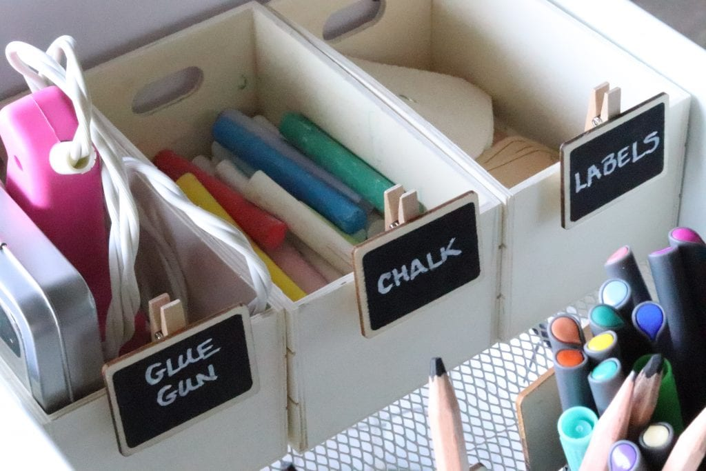 3 small wood crates labeled and holding a pink glue gun, colored chalk and various labels