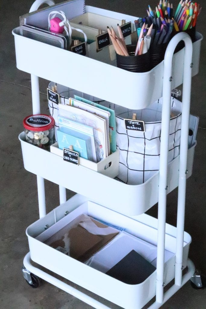 a 3 tier white rolling cart holding organized and labeled craft supplies