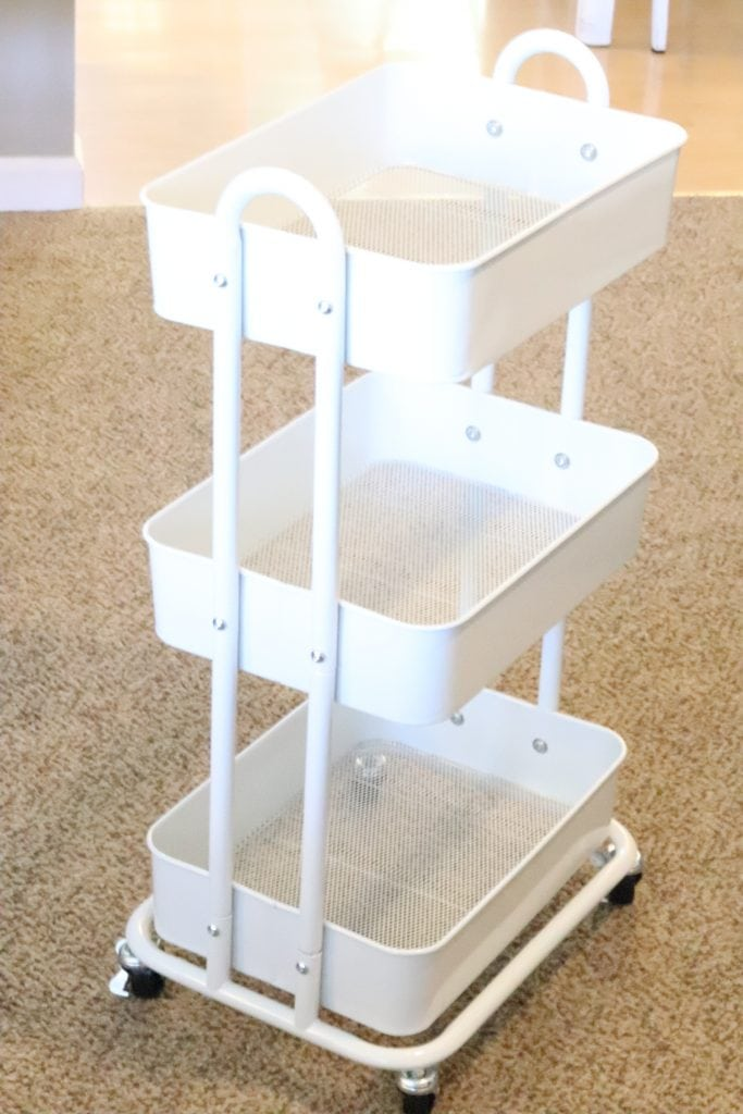 empty white 3 tier rolling cart sitting on brown carpet