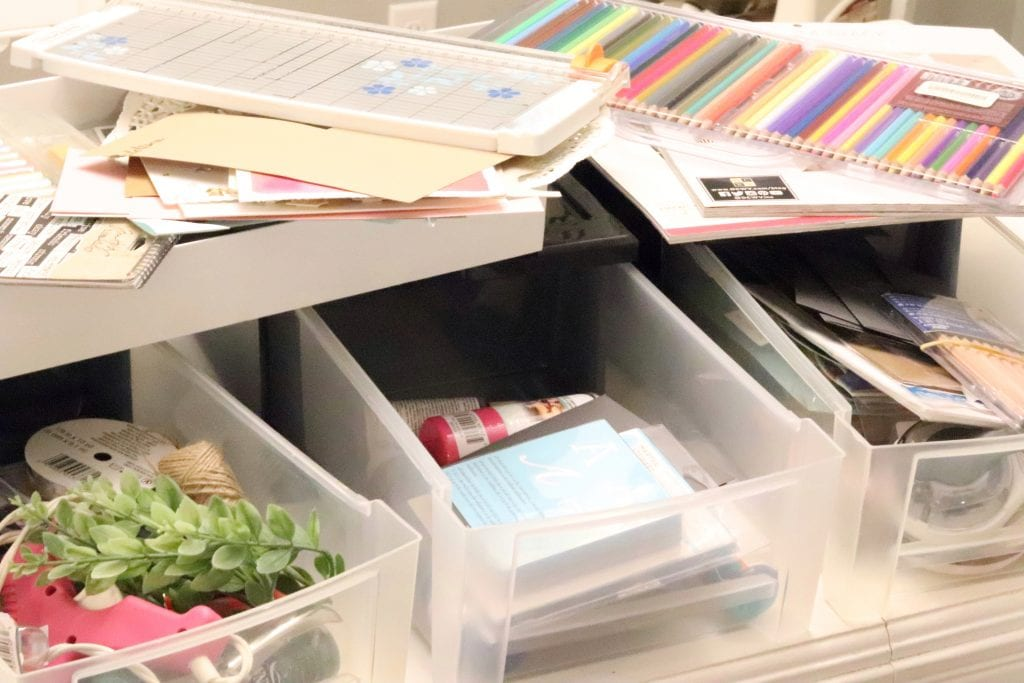 Open plastic containers holding craft supplies like colored pencils, stencils, fake greenery and a pink glue gun