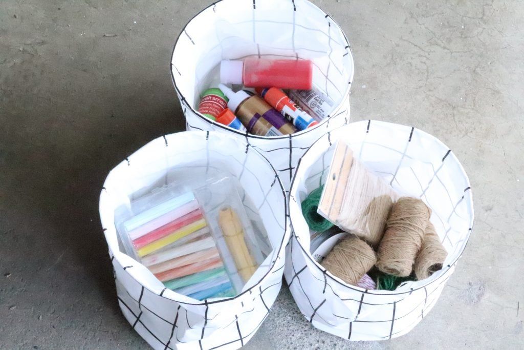 3 collapsible black and white round bins holding chalk, jute string and paint and glue
