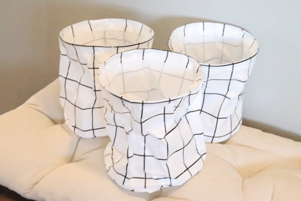 3 black and white round collapsible bins sitting on a cream-colored cushion