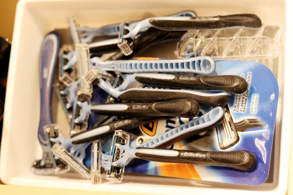 a pile of blue and black shaving razors sitting in a white container